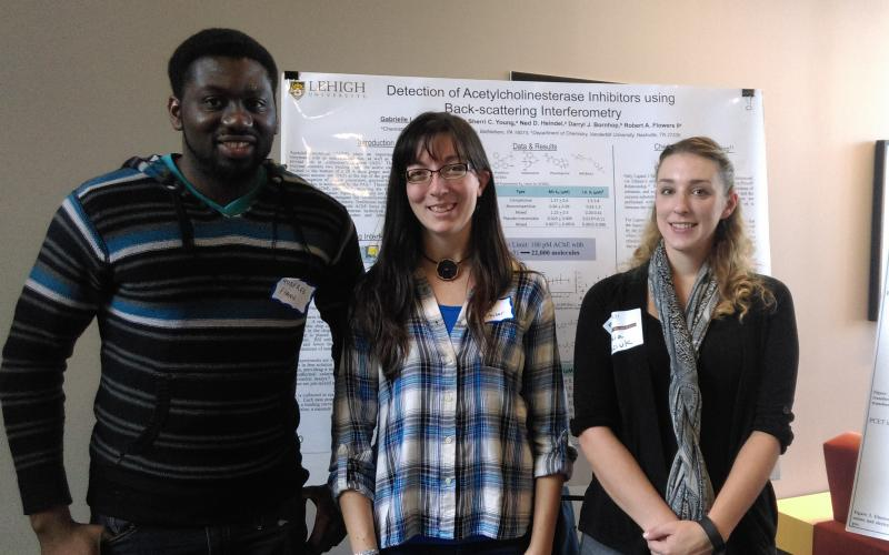 Senior group members, Godfred, Gaby, and Tesia display their research at the Graduate Student Open House.